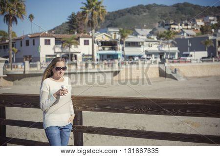 Beautiful woman drinking her morning coffee walking along boardwalk