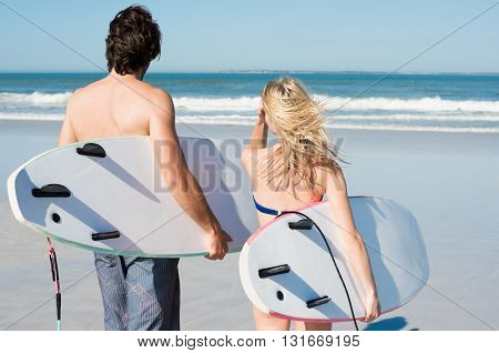 Surfers ready to swim in the sea. Portrait of couple holding surfboard under their arms. Rear view of couple with surfboards walking at the beach.