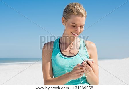 Young woman listening to music during workout. Runner woman checking her song with mp3 player while resting from routine exercise. Happy young jogger listening to music at beach.
