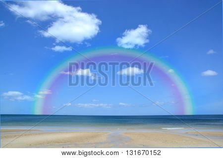Colorful rainbow over a Tropical beach of Andaman Sea Thailand