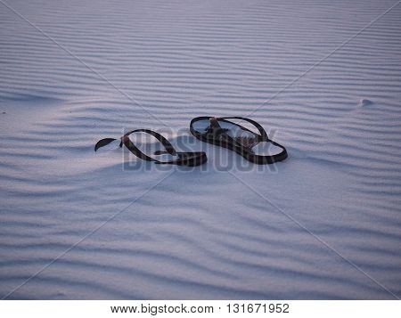 Lonely Pair of Sandals Buried in the Sand