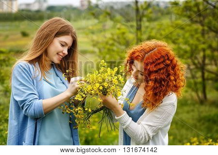 Best friends forever. Girlfriends weave a wreath of wild flowers in the park. BFF.