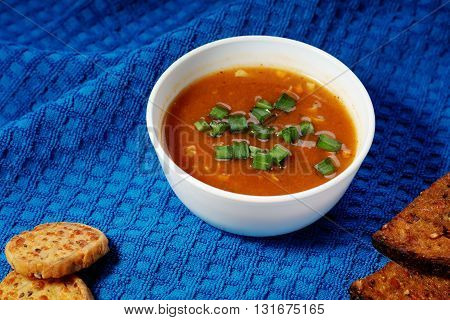 Goulash soup and sliced bread on a  towel