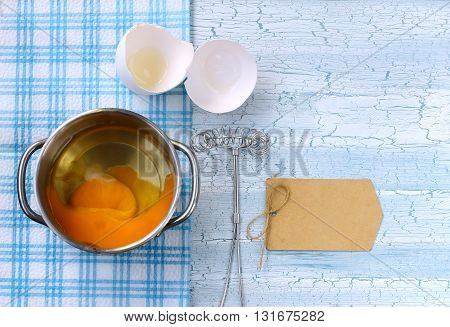 Fresh broken raw egg in pan whisk for whipping paper tag on wooden table