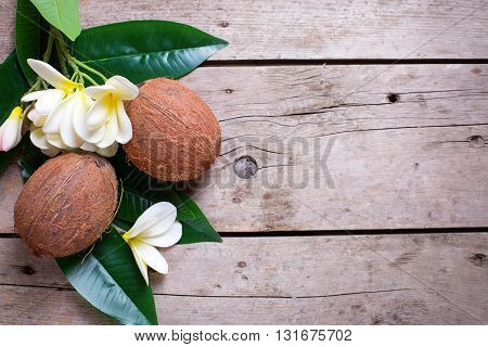 Two coconuts on leaves and plumeria flowers on aged wooden background. Selective focus. Flat lay. Top view with copy space.
