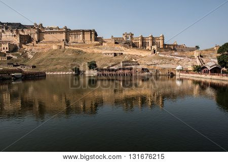 View of the Maota lake and beautifully decorated Amber Fort palace in Jaipur, Rajasthan. The lush green Aravalli hill range is also seen on the background.