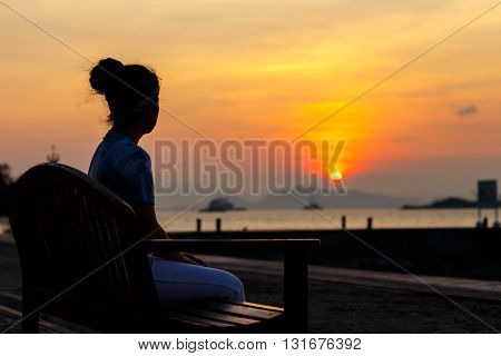 silhouette young woman sitting wood chair waiting for somthing at beautiful sunset background