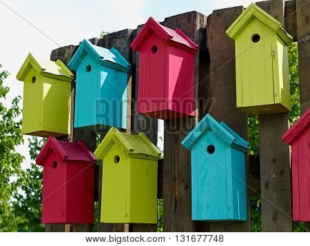 Colorful creative wooden nesting boxes birdhouse hanged on a wall in backyard