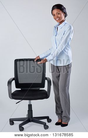 Pretty friendly african black woman showing a vacant office chair, recruitment hiring employment concept