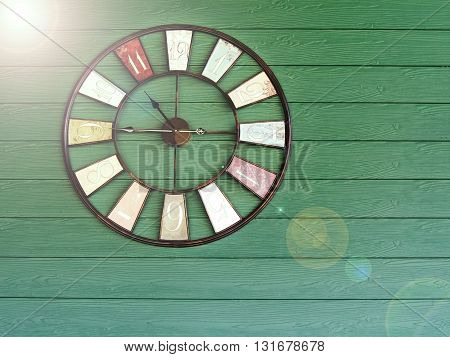 Old vintage with flare clock on green wooden plank wall background. Time management concept.