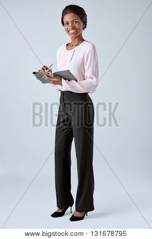 Beautiful black african corporate business woman writing into an organiser, keeping notes
