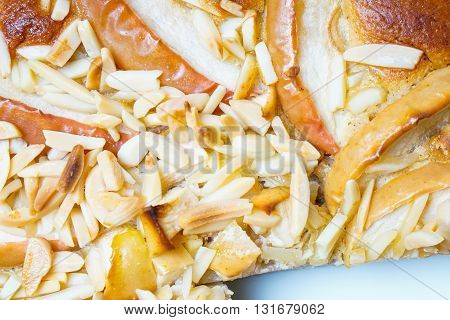 Apple pie with almonds served on a white plate