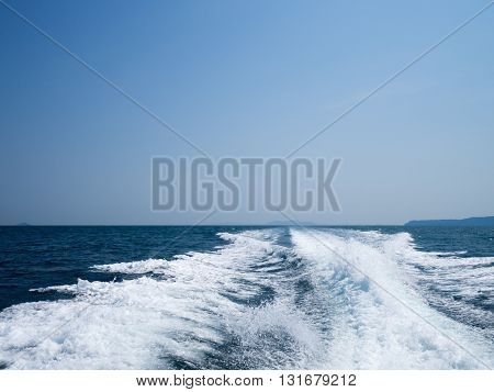 Restless foamy blue sea wake water on the sea water surface with clear blue sky while travel by speed boat in the ocean.