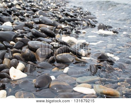 Sun reflections on pebble stones on the beach and sea water.