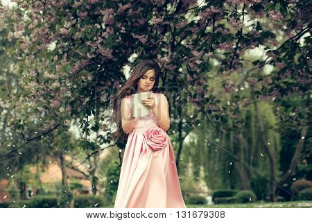 Girl In Dress With Notebook And Pen In Garden