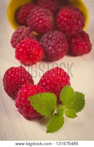 Vintage photo Fresh raspberries and leaf of lemon balm on white wooden table concept of healthy food and dessert