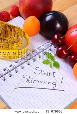 Fresh fruits and vegetables with tape measure and notebook for writing notes concept of slimming diet and healthy nutrition