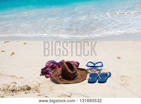 The straw hat, mask, sun glasses and flip flops on a tropical beach