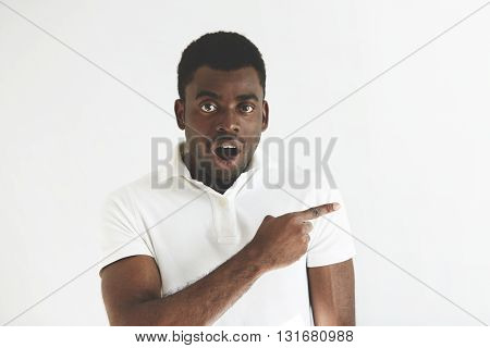 Portrait Of Shocked Or Astonished Young Black Male With Mouth Wide Open, In White Polo Shirt, Showin