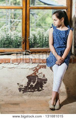 Serious Girl Sitting Near Window