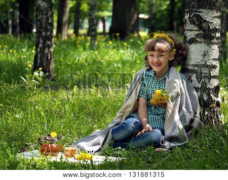 Girl picnic. She laughs. Green grass, birch. Bouquet of wildflowers. On board the tea, a cup of tea. The concept of outdoor recreation, relaxation, happiness and joy