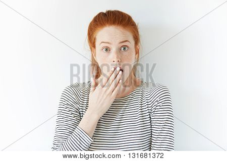 Close Up Isolated Portrait Of Shocked Young Redhead Woman Wearing Striped Top, Covering Mouth With H