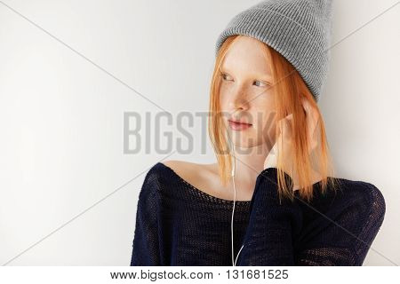 Isolated Headshot Of Attractive Hipster Young Female Listening To Her Favorite Music With Earphones.