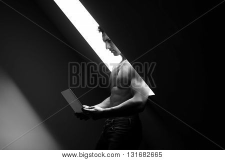 Sexy young man with muscular body and bare torso posing near window holding laptop black and white