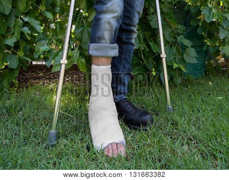 Young Man With A Leg Cast In A Garden