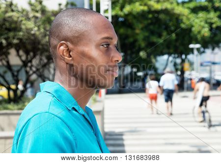 African american man in bright shirt looking sideways outdoor in the city in the summer