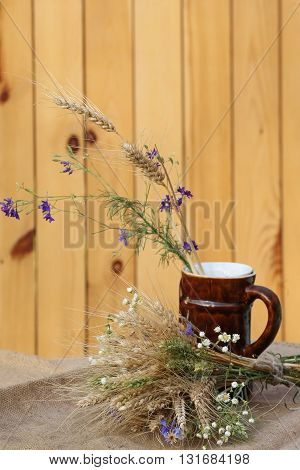 bouquet of ears of rye and wildflowers on a background of wooden planks