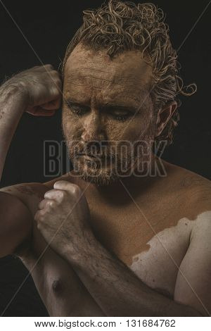 Violence, covered with mud all over her naked body on black background man. adventure and risk, competition force