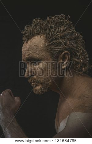 Muscular, covered with mud all over her naked body on black background man. adventure and risk, competition force