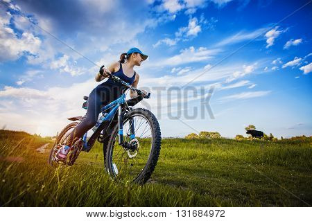 Happy woman cyclist rideson the meadow on a mountain bike. Adventure travel. wide angle