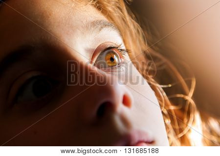 A close up image of a little girl's brown eye in the sun. She is pulling her head back and seems to be afraid of something.