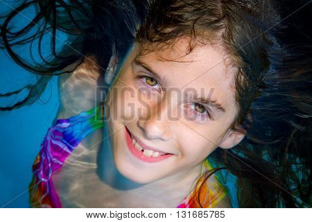 A tween girl looks up from a swimming pool and smiles with big eyes and buck teeth.