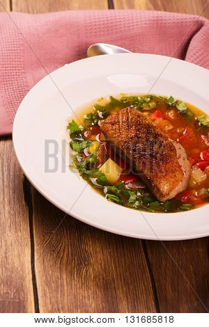 Spanish hot vegetable soup with duck breast. Rustic style. Toned image