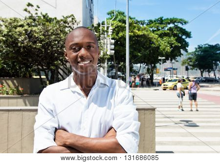 African american man in white shirt with crossed arms outdoor in the city in the summer