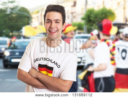 Laughing fan in german jersey with other fans in the background