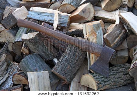 Old axe on stack firewood logs texture background