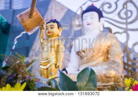 Bathing of a golden statue of the Buddha. The bathing of Buddha statues is a traditional wish ceremony in Buddhism on Buddha's birthday