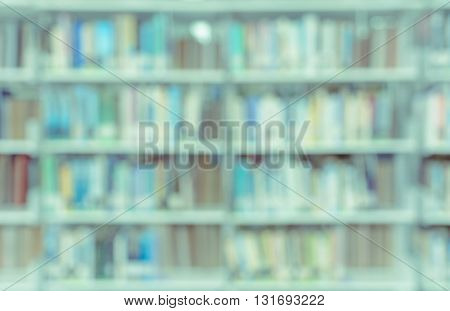 Blurred abstract background of bookshelves and interior of college or university library with textbooks and literature
