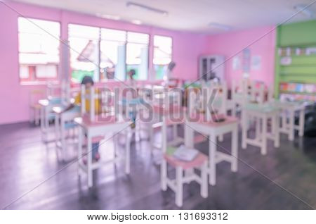 Blur abstract image background of school classroom with colorful wooden tables and chairs