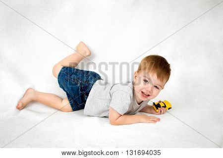 A sweet looking little boy plays happily with a toy car. He is laying on his tummy but kicks his foot up in excitement as he turns to see the camera.