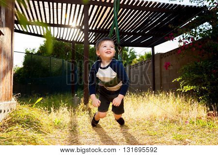 A young boy lays on his belly on a swing and twists it up so that he can spin. He looks excited.