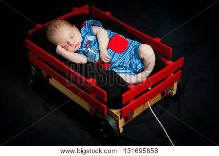 A newborn baby boy sweetly sleeps in a little red wagon. He has an arm curled up by his face and is wearing a blue jumper.