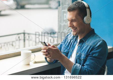 Attractive young man is holding a mobile phone and smiling. He is listening to music from headphones. The man is sitting near a window