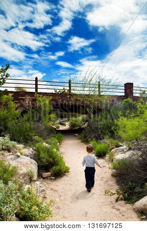 Toddler boy explores a desert path. He walks boldly towards a bridge under a bright blue and cloudy sky. The image has a dreamy nostalgic look.