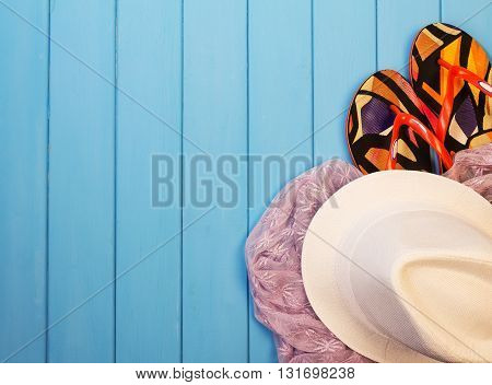Beach accessories: hat, flip flops and sarongs on the background of wood painted in blue.