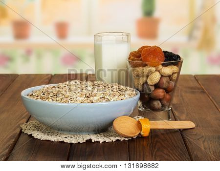 Healthy food for adults: a bowl of oatmeal, a glass of milk, nuts, dried fruit and a wooden spoon on a background of the kitchen.
